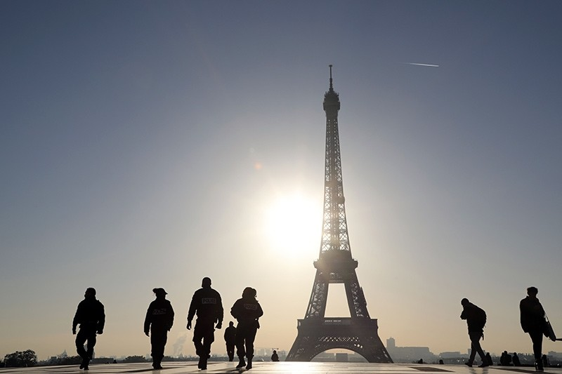 French police officers (L) patrol across the Trocadero plaza opposite the Eiffel Tower, at sunrise on November 7, 2017 in Paris (AFP Photo)