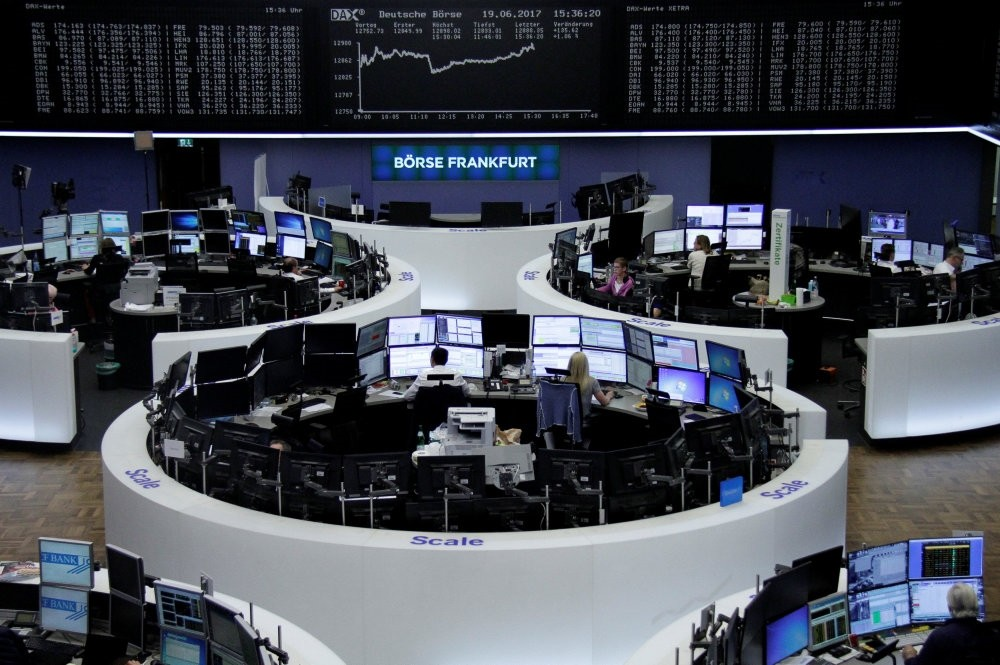 Traders work in front of the German share price index, DAX board, at the stock exchange in Frankfurt.