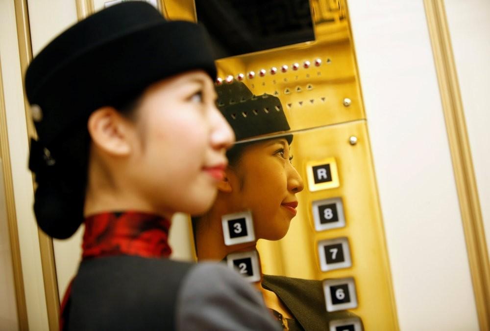 Elevator operator Yuria Nagamoto works at Takashimaya department store in Tokyo, Oct. 18.