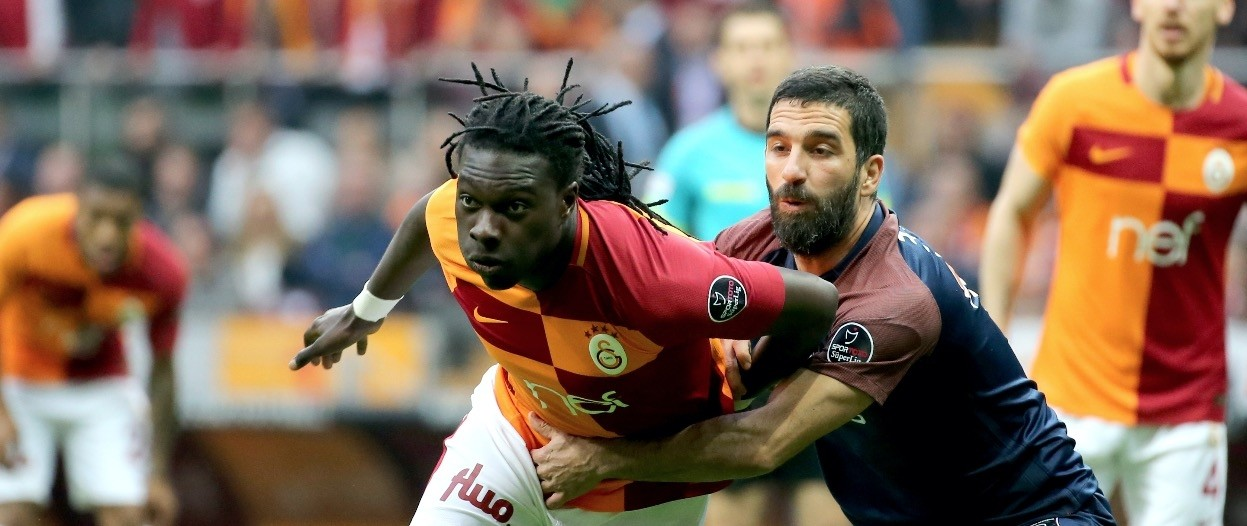 Galatasaray's Bafetimbi Gomis (L) and Medipol Bau015faku015fehir's Arda Turan vie for ball during the match at Tu00fcrk Telekom Arena, Istanbul.