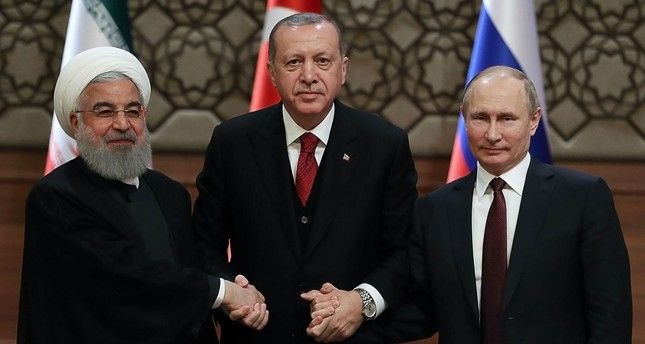 President Recep Tayyip Erdoğan, Iran's President Hassan Rouhani, and Russia's President Vladimir Putin shake hands after a joint press conference as part of a tripartite summit on Syria, in Ankara, April 4.