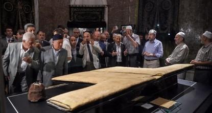 pEine lange Schlange von Männern und Frauen, die in getrennten Linien stehen, warten geduldig an einer Istanbuler Moschee, um ein Jahrhunderte altes Kleidungsstück sehen zu können. Es handelt sich...