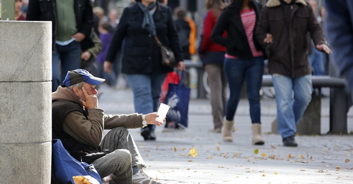 A man begs as pedestrians walk past at Wilmersdorfer shopping street in Berlin October 9, 2012 (Reuters Photo)