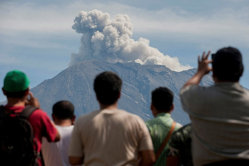 People watch as Mount Agung spews ash and smoke during an eruption from an obeservation post in Rendang, Karangasem, Bali, Indonesia December 9, 2017 in this photo taken by Antara Foto. (Reuters Photo)