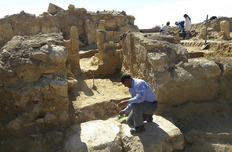 This undated photo released by the Egyptian Ministry of Antiquities shows archeologists working at the site of the remains of a temple dating back to the Greco-Roman period in the country's western desert, some 50km west of Siwa Oasis. (AP Photo)