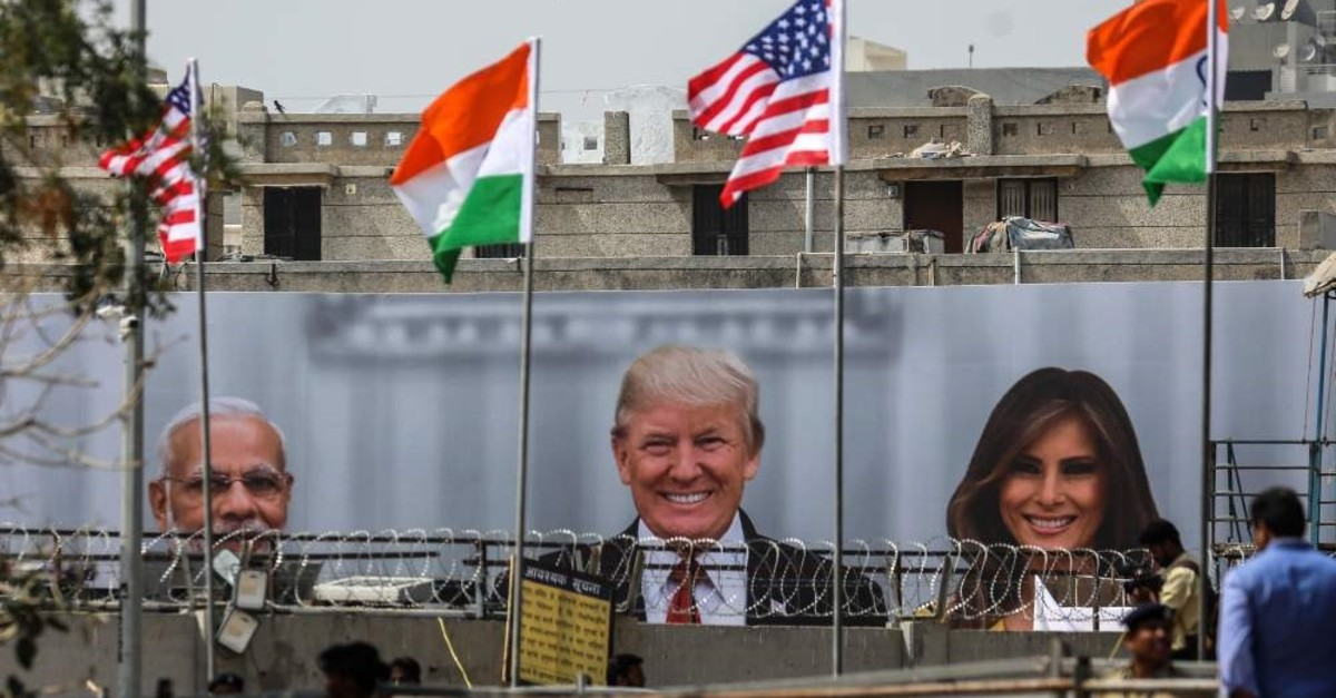 Policemen stand guard near the billboard showing (L-R) India's Prime Minister Narendra Modi, U.S. President Donald J. Trump and first lady Melania Trump, outside the Sardar Patel Gujarat Stadium ahead of an upcoming state visit by the U.S. president, in Ahmedabad, India, Feb. 23, 2020. (EPA Photo)