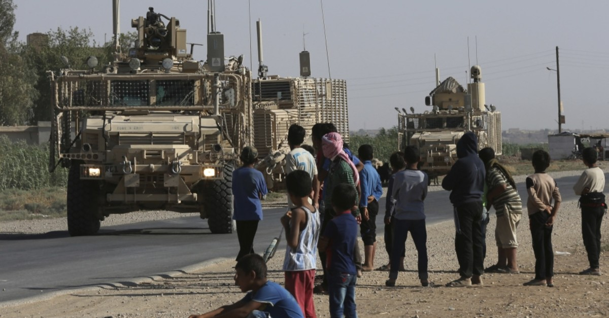 Syrians watch a U.S. armored convoy pass by on a road to the northeastern Raqqa province, July 26, 2017.