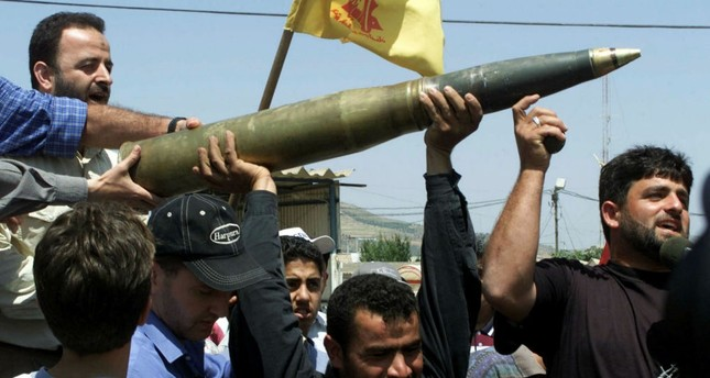 Lebanese demonstrations hold up an Israeli tank shell left behind by withdrawing Israeli troops along the Israel-Lebanon border near Metulla.