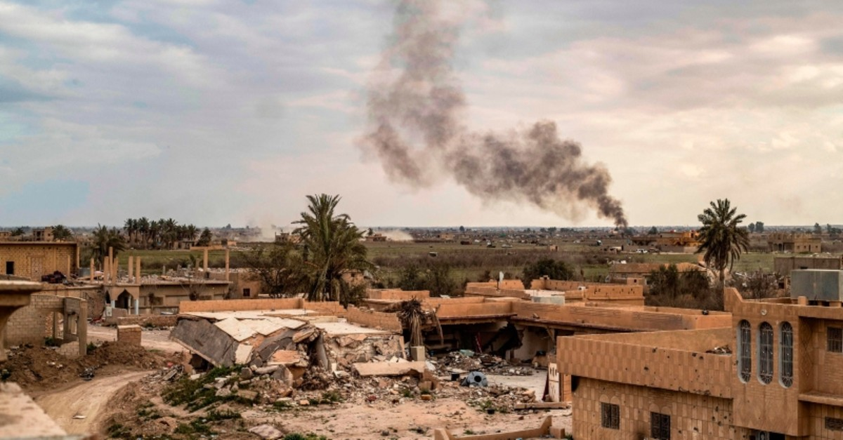 Smoke plumes billow from the remains of a Daesh terror group camp near the village of Baghouz in the eastern Syrian province of Deir el-Zour, on March 15, 2019. (AFP Photo)