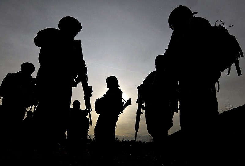 This photo taken on February 28, 2009 shows US soldiers with the NATO-led International Security Assistance Force (ISAF) silhouetted as they walk during a patrol outside Bagram Airbase, some 50 km north of Kabul. (AFP Photo)