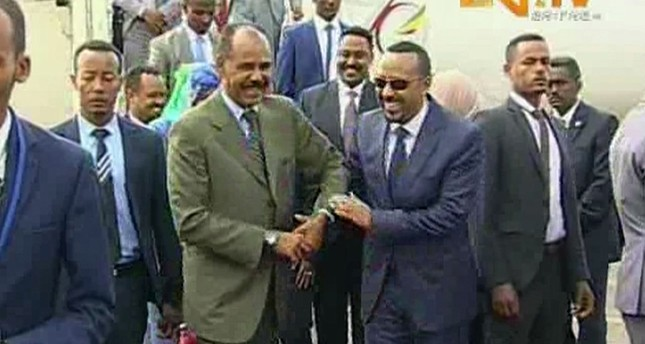 In this grab taken from video provided by ERITV, Ethiopia's Prime Minister Abiy Ahmed, centre right is welcomed by Erirea's President Isaias Afwerki as he disembarks the plane, in Asmara, Eritrea, Sunday, July 8, 2018. (ERITV via AP)