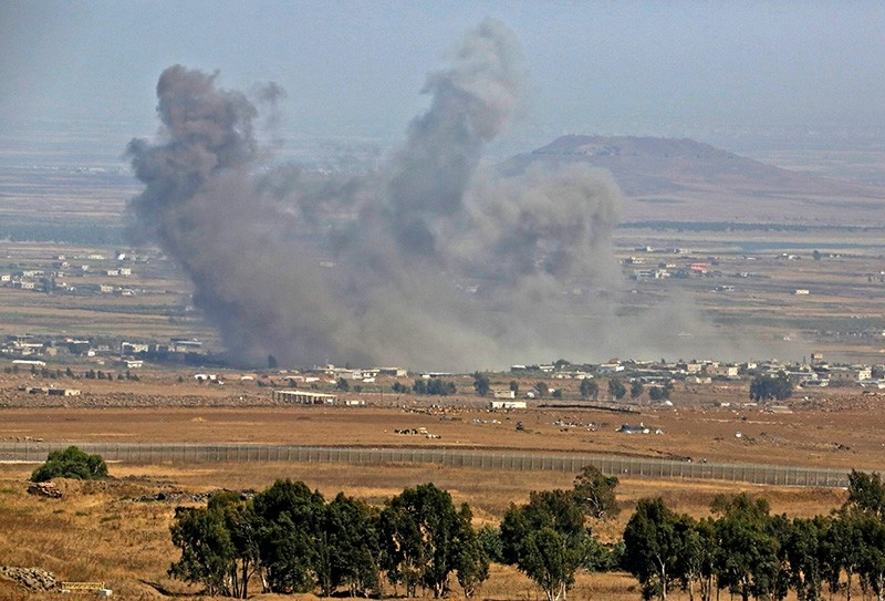 A picture taken on July 19, 2018 from the Israeli-annexed Syrian Golan Heights shows smoke rising in an area where Russian-backed government forces in Syria have been carrying air strikes in the southern Syrian province of Daraa. (AFP Photo)