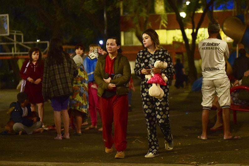 Residents stand out in the street following a 5.9 magnitude quake in Mexico City early on Feb. 19, 2018. (AFP Photo)