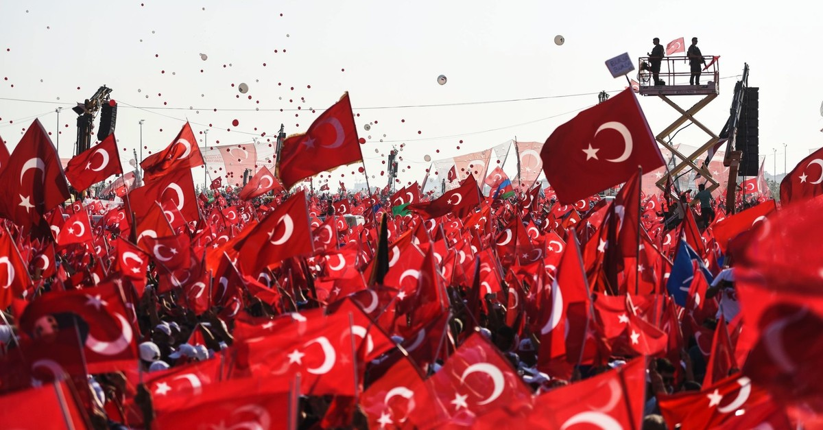 Turkish people wave Turkish national flags as they stand in front of giant screens and Turkish special force police officers standing guard in Istanbul during a rally against the July 15, 2016 failed coup attempt, Aug. 7, 2016.