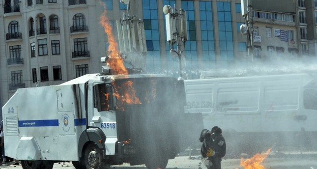 A rioter wearing a gas mask runs after rioters set a police vehicle on fire at Taksim Square adjacent to Gezi Park, June 11, 2013.