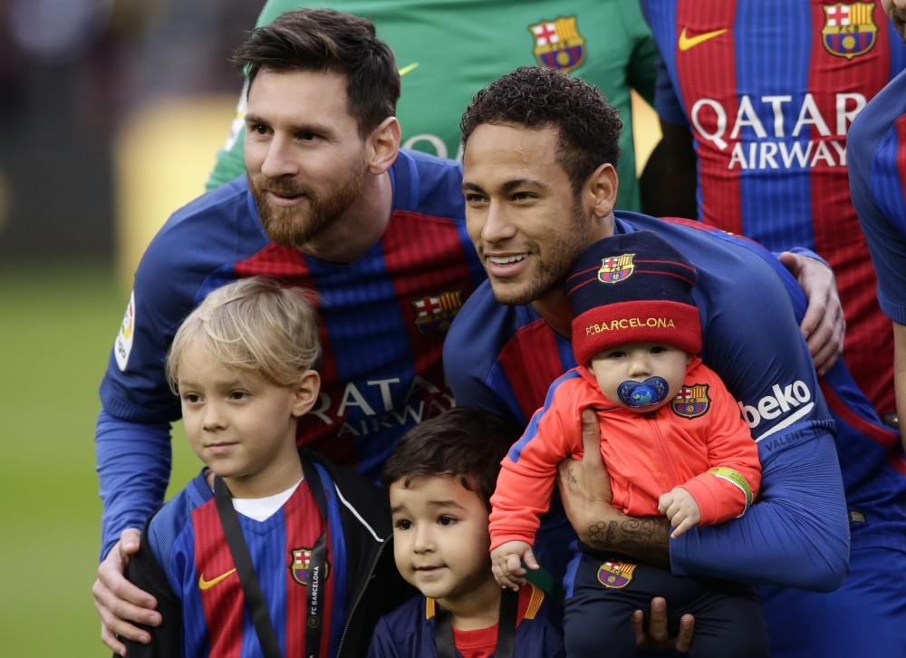 Barcelonau2019s Neymar, right, poses with his son Davi Lucca, left front, next to his teammate Lionel Messi, left, and other children prior of the Spanish La Liga match between Barcelona and Athletic Bilbao at the Camp Nou in Barcelona.