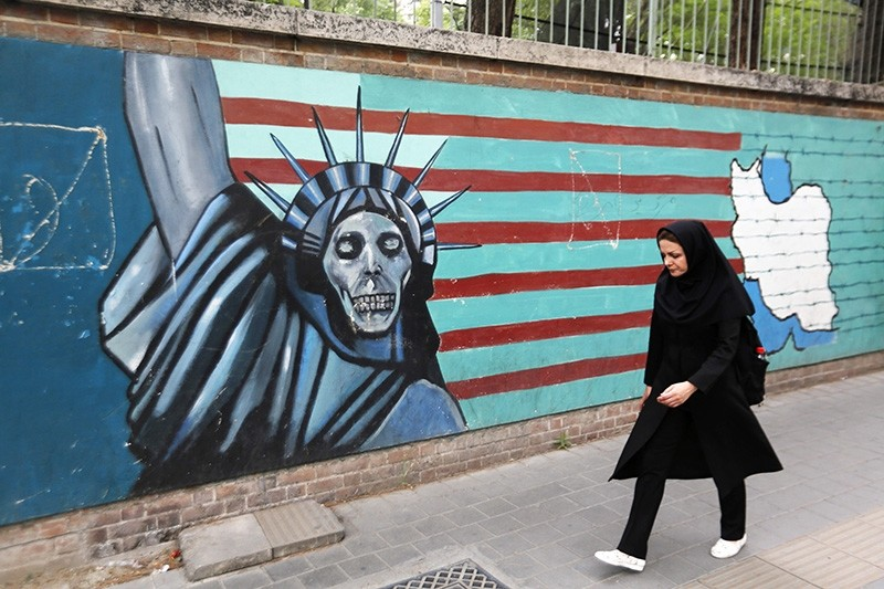 An Iranian woman walks past a mural on the wall of the former US embassy in the Iranian capital Tehran on May 8, 2018. (AFP Photo)
