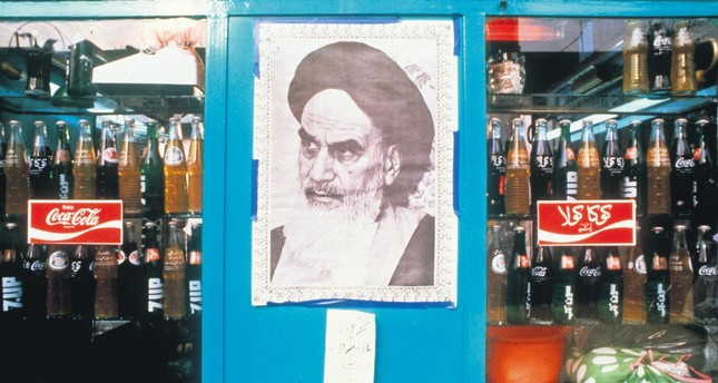 A poster of Ayatollah Ruhollah Khomeini, the founder of the Islamic Republic of Iran, in a shop window next to bottles of Coca-Cola, Tehran, Iran, Jan. 1, 1979.