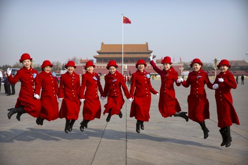 Bus ushers leap as they pose for a group photo in Tiananmen Square during a plenary session of the National Peopleu2019s Congress in Beijing.