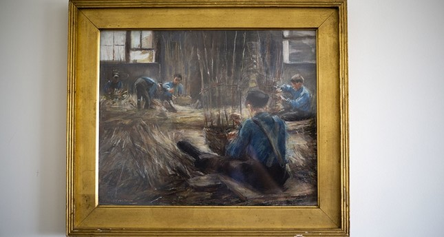 In this photo taken on Wednesday, April 5, 2017, Max Liebermann's Basket Weavers painting hangs in a law office in Jerusalem. (AP Photo)