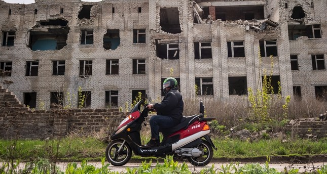 A cyclist rides his motorbike near a destroyed hospital, Slovyansk, Donetsk region, April 19, 2019.