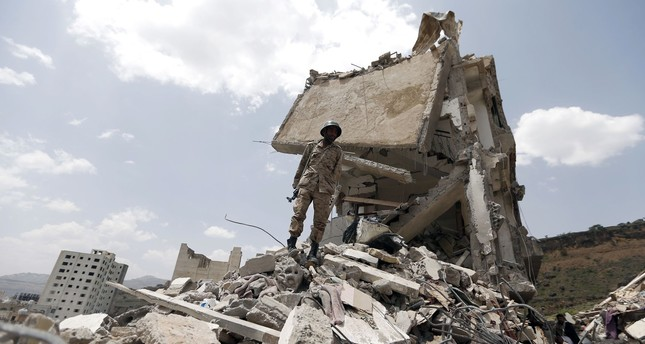 A Yemeni soldier stands on the debris of a house, hit in an air strike on a residential district, in the capital Sanaa on August 26, 2017. (AFP Photo)