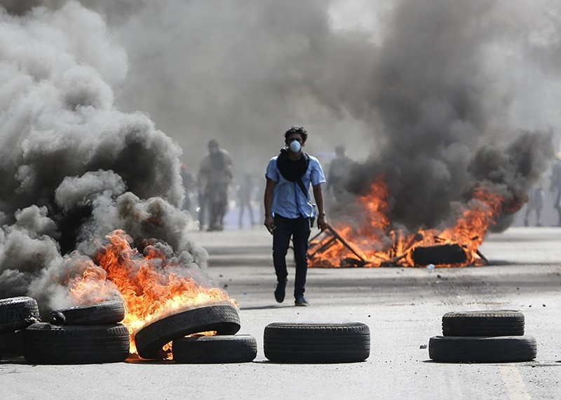 A masked protester walks between burning barricades in Managua, Nicaragua, Friday, April 20, 2018. (AP Photo)