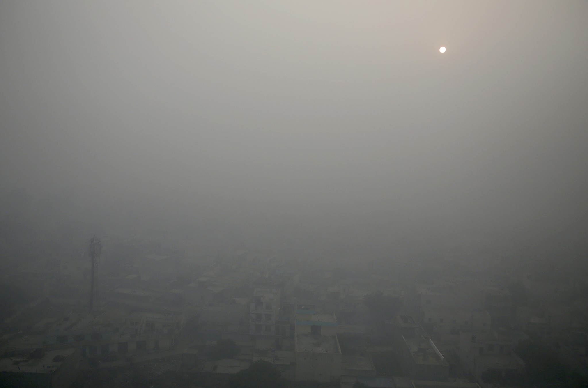 The morning sun is enveloped by a blanket of smog on the outskirts of New Delhi, India. (AP Photo)