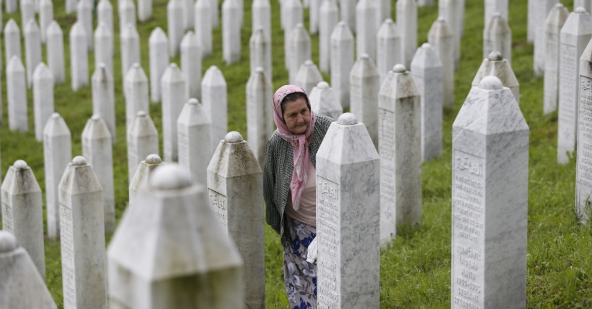 A Bosnian Muslim woman walks among gravestones at the memorial center of Potocari, Srebrenica, July 11, 2018.