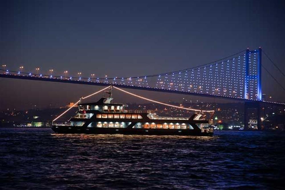 Boat sails on Bosporus at night.