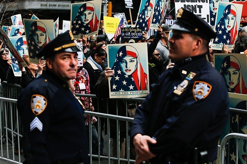 NYPD officers stand by as people take part in a rally called 'I Am A Muslim Too' in a show of solidarity with American Muslims at Times Square on February 19, 2017 (AFP Photo)