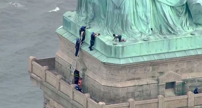 This still image taken from video Courtesy of PIX11 News in New York, shows police talking to a woman who climbed to the base of the Statue of Liberty in New York on July 4, 2018. (AFP Photo)
