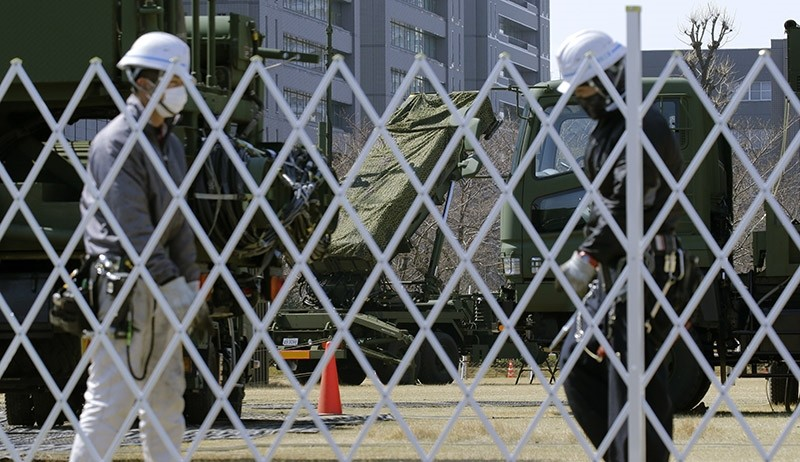 Workers set up a fence around the PAC-3 Patriot missile unit deployed against North Korea's missile firing at the Defense Ministry in Tokyo, Wednesday, March 22, 2017. (AP Photo)