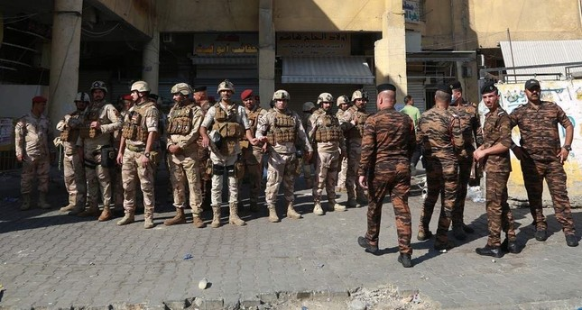 Security forces gather near Iraq's central bank in Baghdad, Iraq, Wednesday, Nov. 6, 2019. Iraqi security forces deployed in large numbers around the bank and began evacuating employees from the building. The protesters did not appear to be heading toward the bank itself. (AP Photo/Khalid Mohammed)
