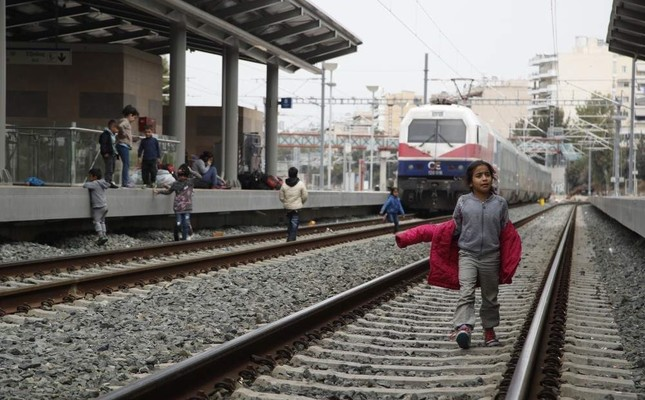 A migrant boy walks at the rail wall that blocked from migrants at the Larissis rail way central station in Athens, April 5, 2019.  AP Photo