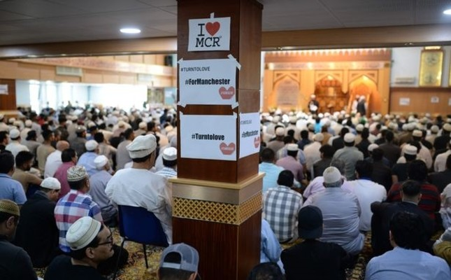 I Love MCR signs for the victims of the Manchester concert attack adorning a pillar as Muslims attend a Friday prayer at the Manchester Central Park Mosque, May 26.