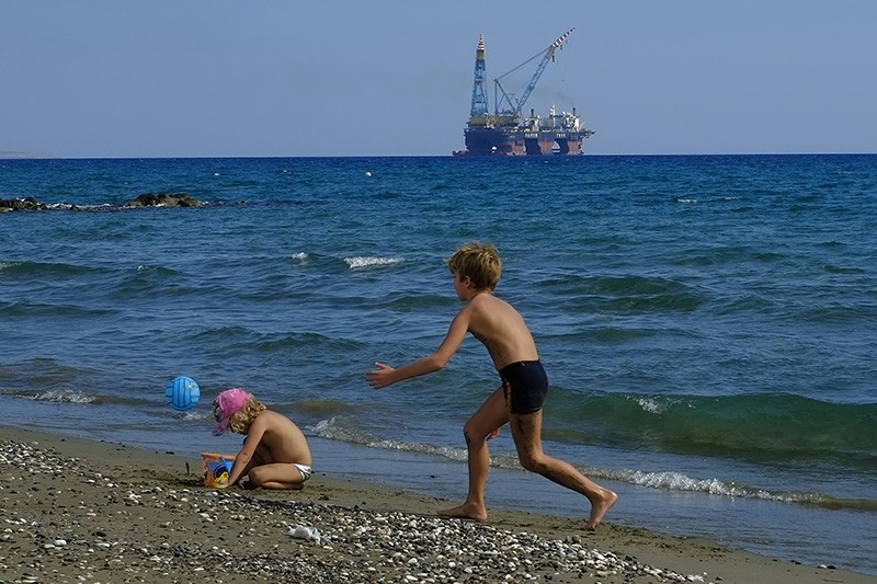 In this photo taken on Sunday, Oct. 15, 2017 children play on a beach with a drilling platform seen in the background, on the outskirts of Larnaca port, in the eastern Mediterranean island of Cyprus. (AP Photo)