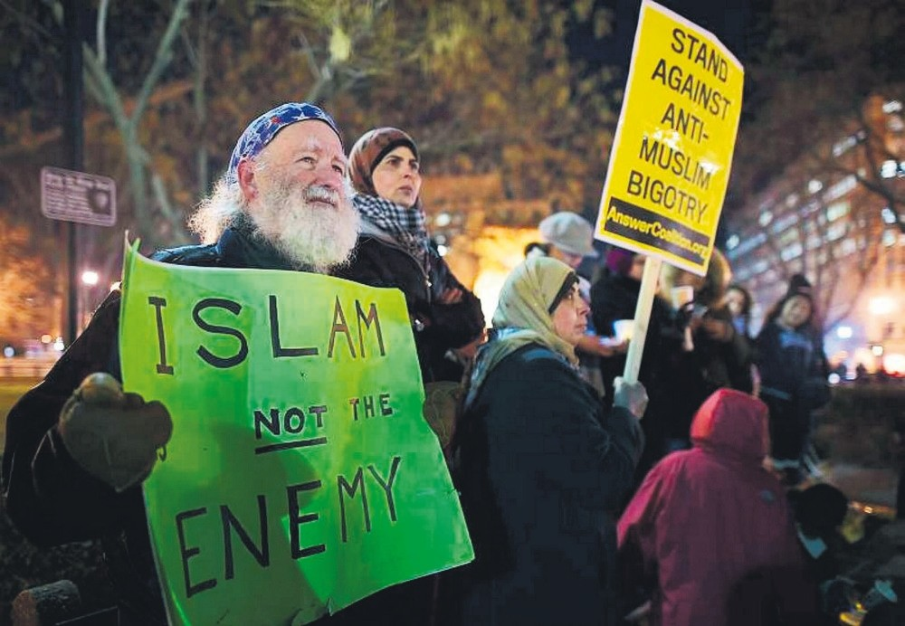 A man holds a placard during a vigil for three young Muslims killed in Chapel Hill, North Carolina, Feb. 12, 2015.
