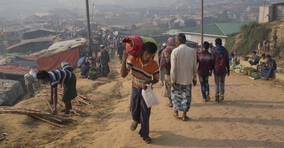 A Rohingya refugee walks with a cooking gas cylinder, Cox's Bazar, Bangladesh, Nov. 17, 2018.