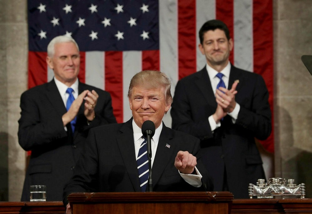 U.S. Vice President Mike Pence (L) and Speaker of the House Paul Ryan (R) applaud as President Donald J. Trump (C) arrives to deliver his first address to a joint session of Congress, Washington, Feb. 28.