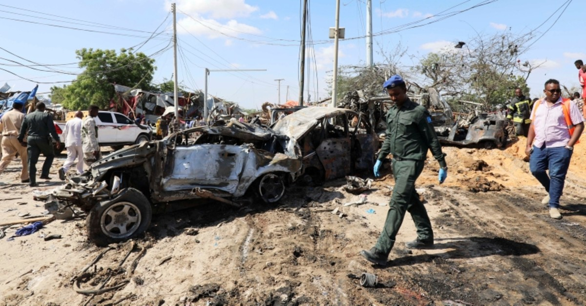 A Somali police officer walks past a wreckage at the scene of a car bomb explosion at a checkpoint in Mogadishu, Somalia  December 28, 2019. (Reuters Photo)
