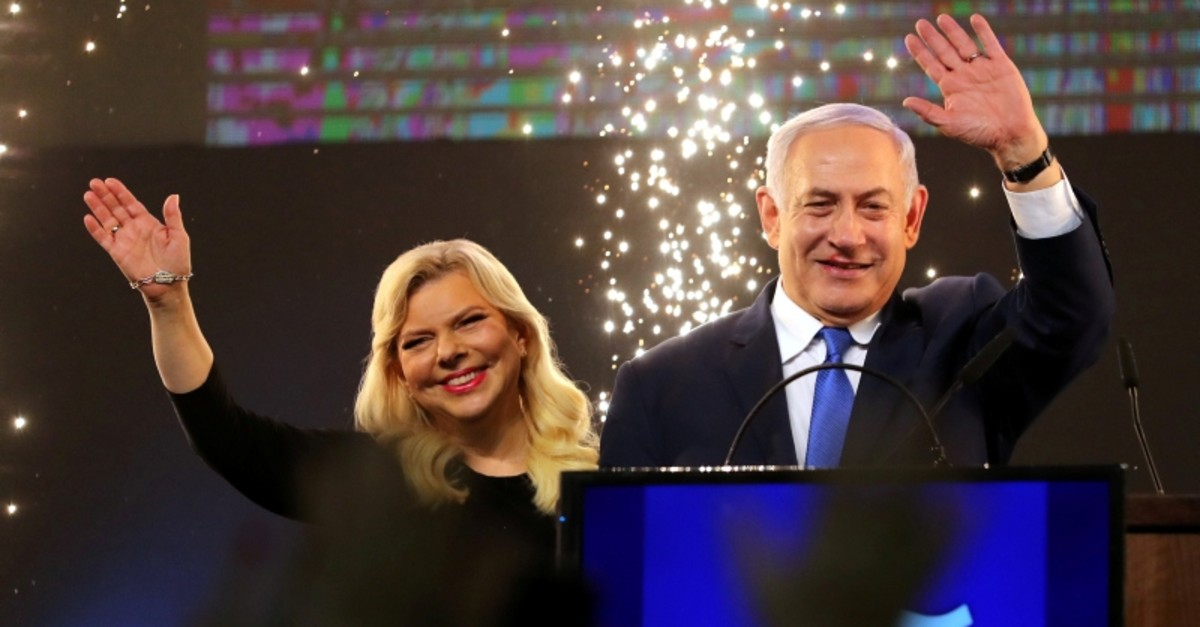 Israeli Prime Minister Benjamin Netanyahu and his wife Sara wave as Netanyahu speaks following the announcement of exit polls in Israel's parliamentary election at the party headquarters in Tel Aviv, Israel April 10, 2019. (Reuters Photo)