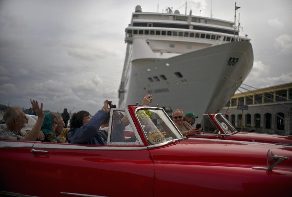 Tourists tour the city in private American classic cars, as they drive in front of a cruise ship in Havana.