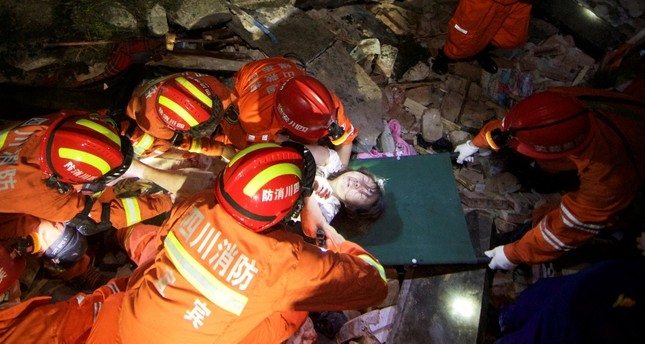 Rescue workers place a woman on a stretcher as they search for survivors in the rubble after earthquakes hit Changning county in Yibin, Sichuan province, China June 18, 2019. (Reuters Photo)