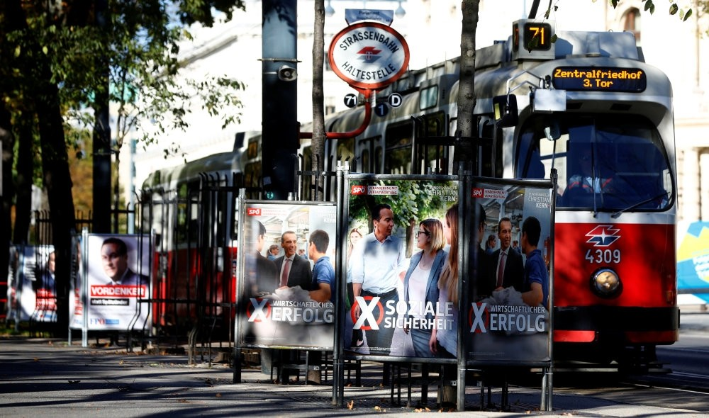 A tram passes an election campaign posters of top candidates from Austrian political parties ahead of the general elections, Vienna, Austria, Oct. 5.
