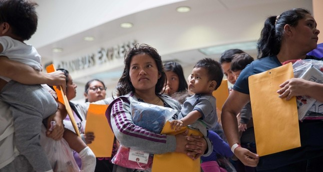 In this file photo taken on June 17, 2018 immigrants wait to head to a nearby Catholic Charities relief center after being dropped off at a bus station shortly after release from detention in McAllen, Texas. (AFP Photo)
