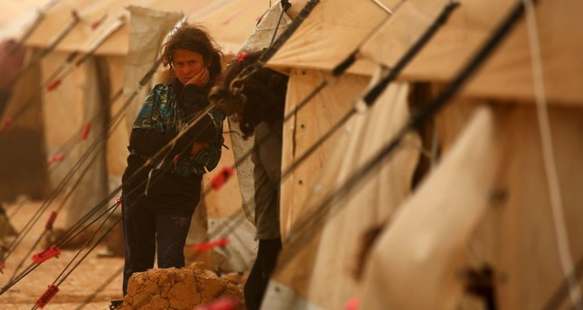 A displaced Syrian girl looking on during a sand storm at the al-Mabrouka camp in the village of Ras al-Ain on the Syria-Turkey border, where many Syrians who fled from their country due to the terrorists groups, shelter on, April 23.