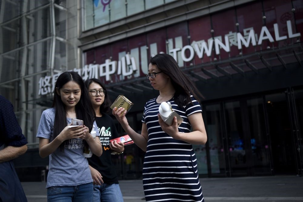 A group of women leave a mall after shopping in Beijing. China's industrial output, a key engine of growth, slowed sharply in July as government efforts to rein in debt weighed on demand and economic activity.
