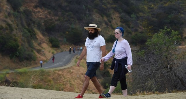Chuck McCarthy chats with his client Anie Dee (R) as they walk in the Hollywood Hills, May 24, 2018 in Runyon Canyon Park in Los Angeles, California (AFP Photo)
