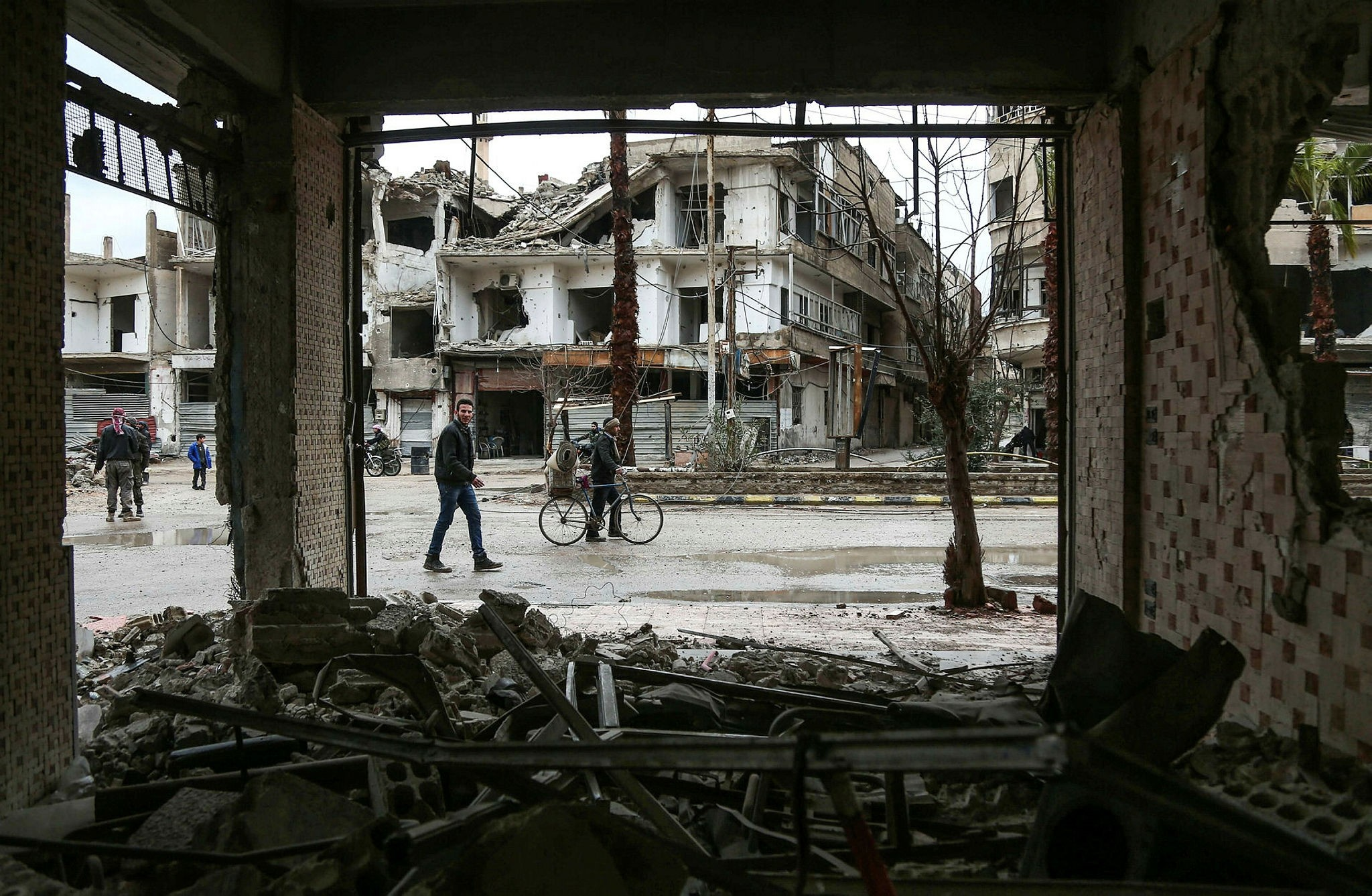Civilians walking past ruins down a rain-soaked street in the Syrian opposition-held enclave of Arbin in Eastern Ghouta near Damascus, Feb. 17.